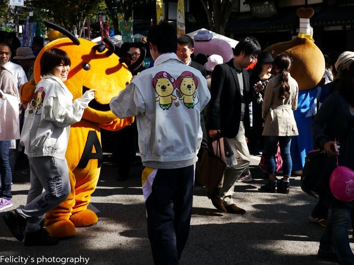 A tiger shaped mascot and his handlers enjoying a rare amount of space.
