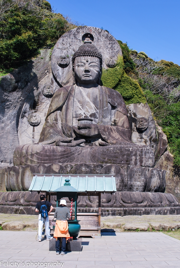 Visitors pay their respects at a small shrine at the feet of the Daibutsu