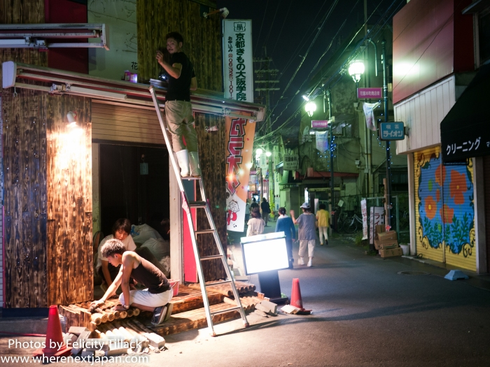 Construction workers fixing up a new karaoke shop smile at a passing photographer.