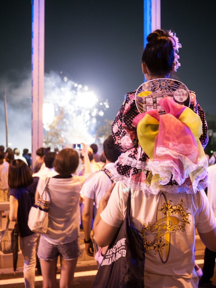 A young girl in her yukata perches on her father's shoulders to get a better view.